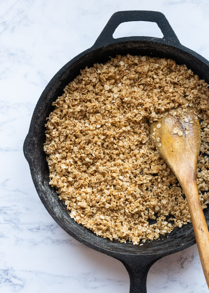 Toasted oats with honey in a cast iron skillet with a wooden spoon.