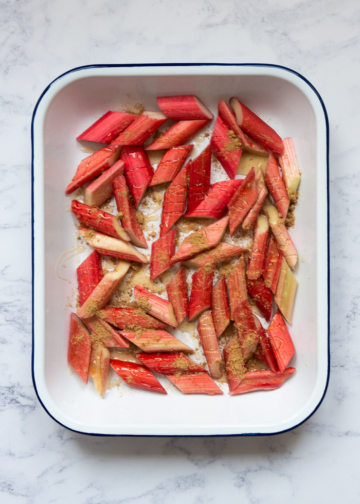 Process Shot 2: Uncooked rhubarb, cut into 1 inch pieces, in an enamel roasting dish with honey and ginger powder on top. Taken from overhead on a marble surface.