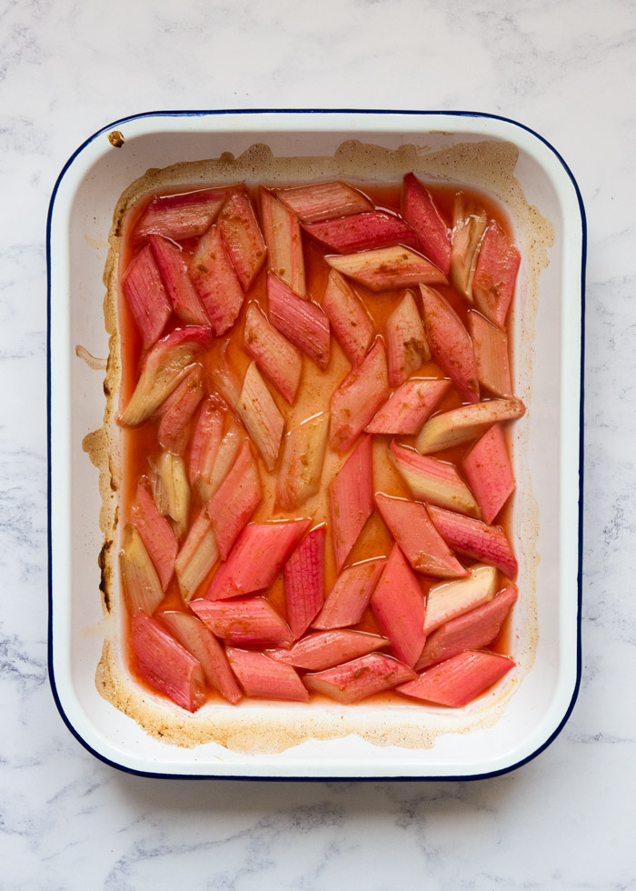 Process Shot 4: Rhubarb that has been roasted in the oven with honey and ginger, in an enamel roasting dish. The rhubarb has released some of its juice and there is some caramelisation around the sides of the roasting dish.