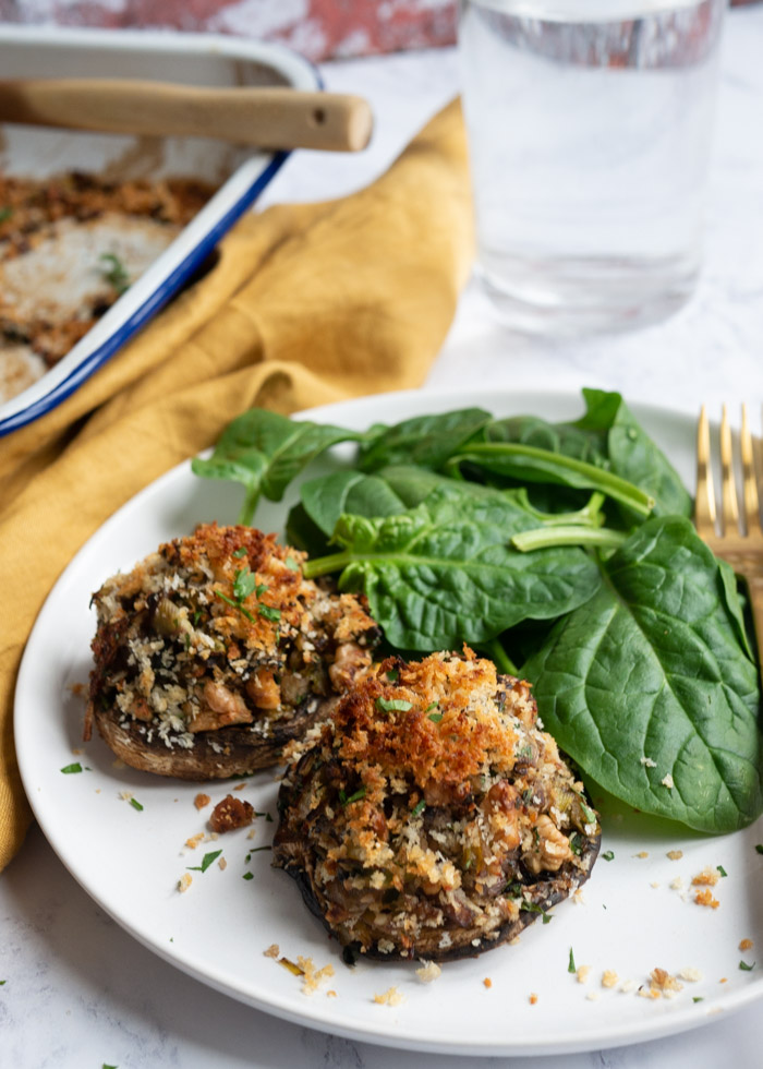 Two stuffed mushrooms on a white plate with spinach leaves and a gold fork.