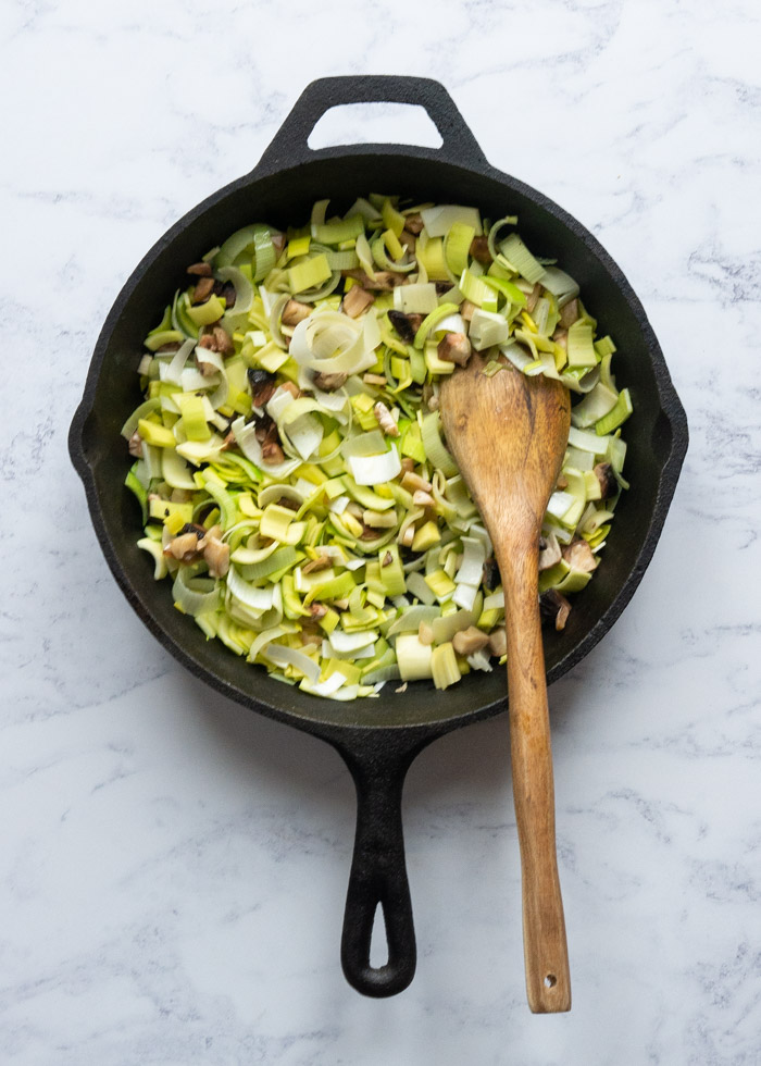 Process shot 2: A cast iron pan with uncooked leeks and mushrooms in it with a wooden spoon.
