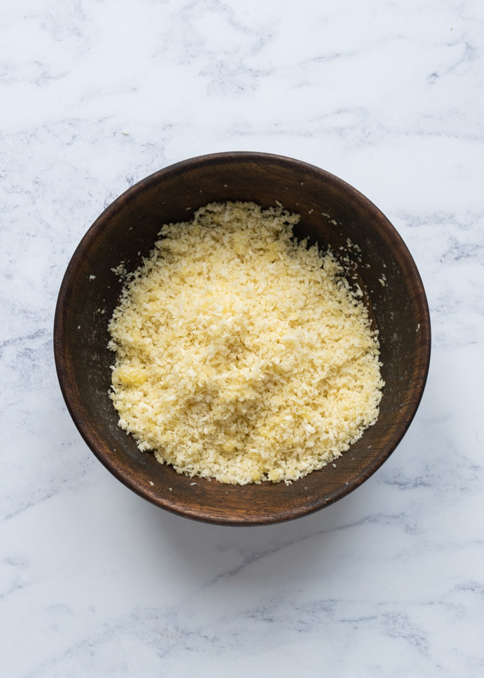 Process shot 3: A wooden bowl filled with a mixture of panko breadcrumbs, parmesan cheese and olive oil.
