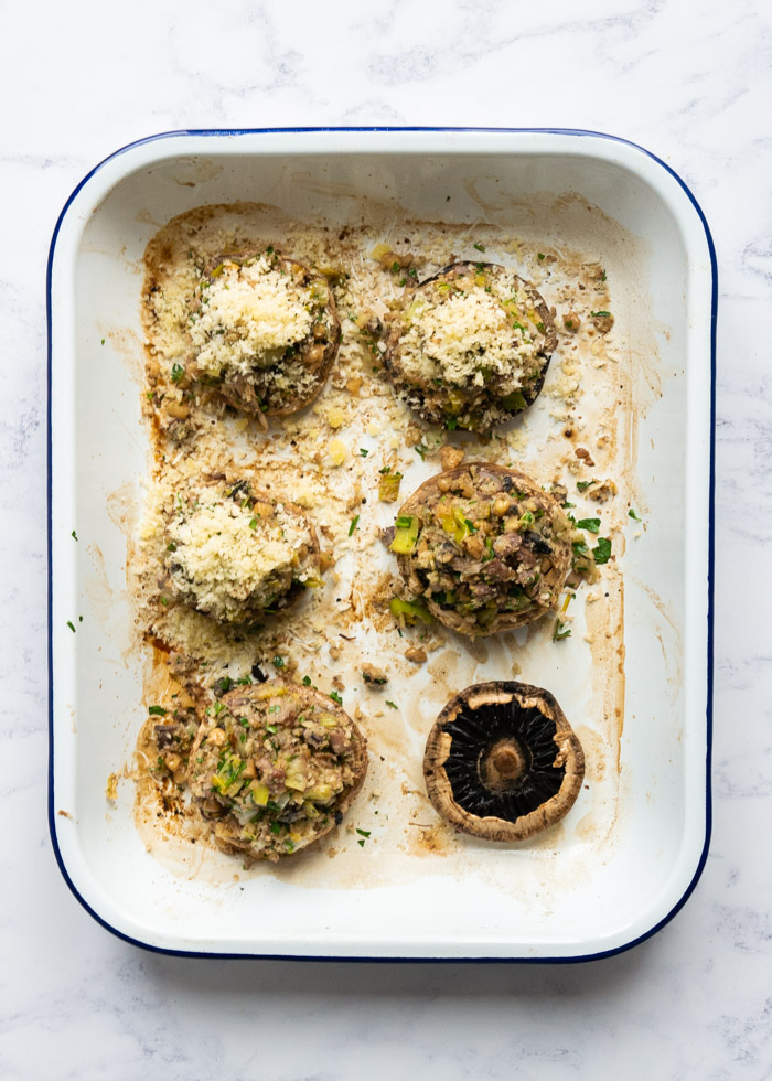 Process shot 6: Six stuffed mushrooms in an enamel roasting tray. Three of the mushrooms are suffed and finished with breadcrumbs, two are just filled with stuffing and one mushroom is yet to be stuffed.