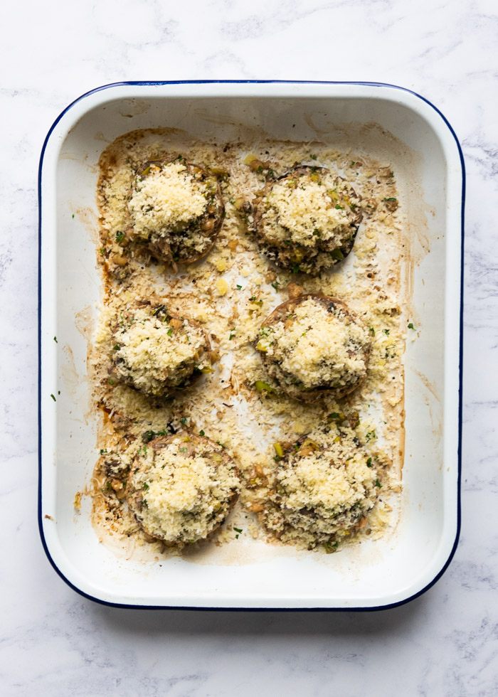 Process shot 7: Six stuffed mushrooms in an enamel roasting tray, before going into the oven to be cooked.