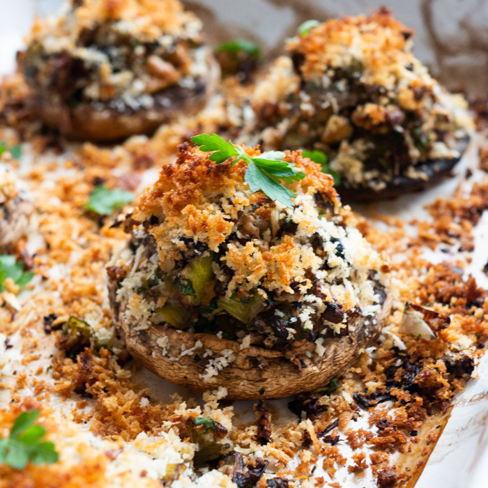 A close up of a stuffed mushroom in an enamel roasting tin. The breadcrumbs on top are golden brown and there is a small leaf of parsley on top