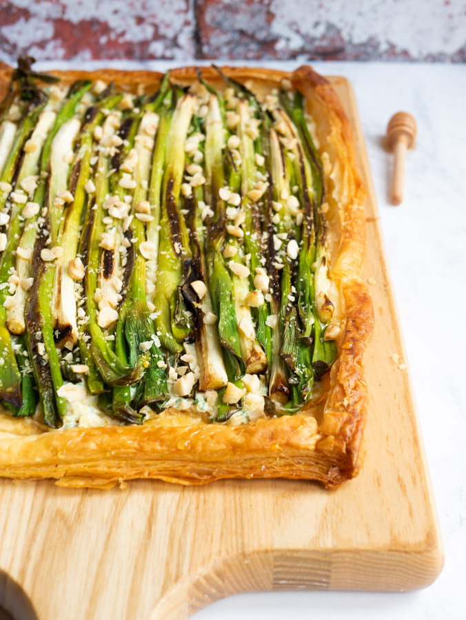 A charred spring onion puff pastry tart on a wooden chopping board. To the right of the chopping board is a wooden honey drizzler.