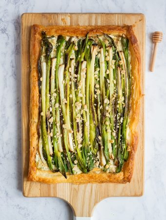 An overhead photograph of A charred spring onion puff pastry tart on a wooden chopping board. To the right of the chopping board is a wooden honey drizzler.