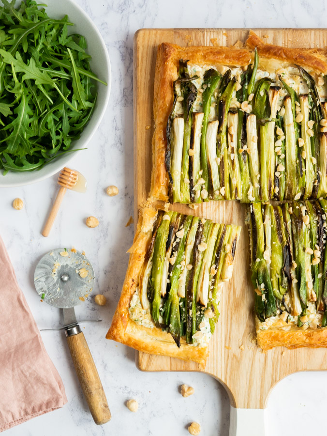 The spring onion tart is sitting on a wooden chopping board. A slice has been cut and pulled away from the rest of the tart. To the left of the chopping board is a pizza butter with a wooden hadle which has been used to cut the tart. There is also a honey drizzler, a bowl of rocket leaves and several hazelnuts around the chopping board.