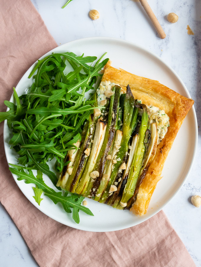 A slice of charred spring onion tart on a white plate with a handful of rocket leaves. The plate is sitting on a pink napkin and there are several hazelnuts around the plate.