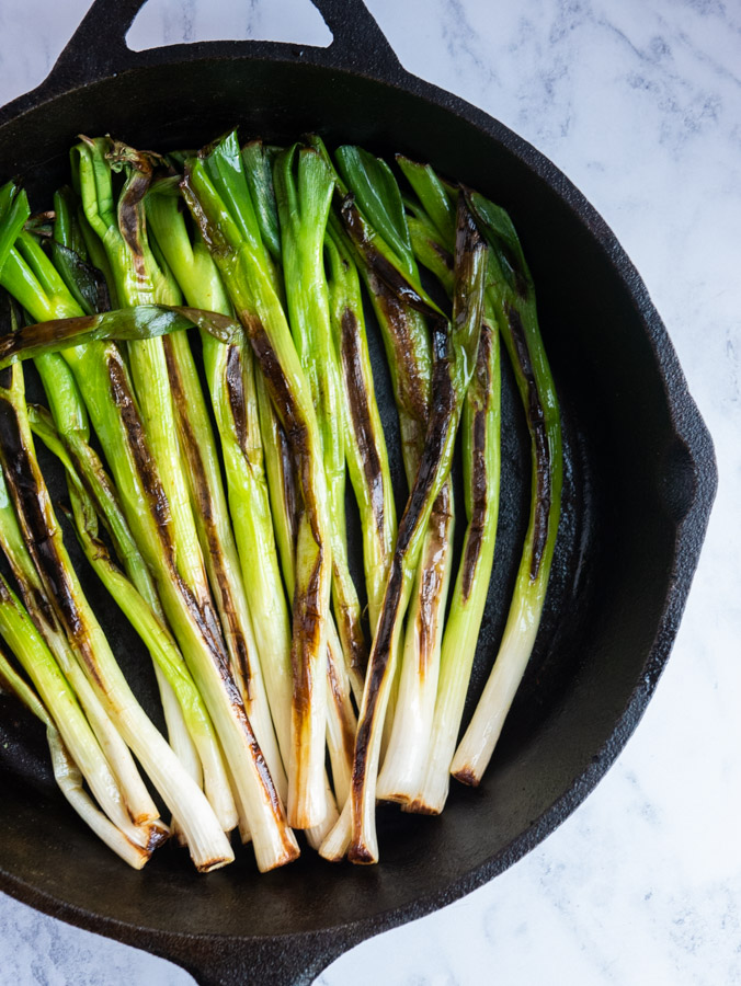 Charred spring onions is a cast iron frying pan.