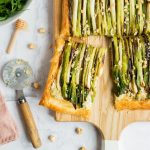 The spring onion tart is sitting on a wooden chopping board. A slice has been cut and pulled away from the rest of the tart. To the left of the chopping board is a pizza butter with a wooden hadle which has been used to cut the tart. There is also a honey drizzler and several hazelnuts around the chopping board.