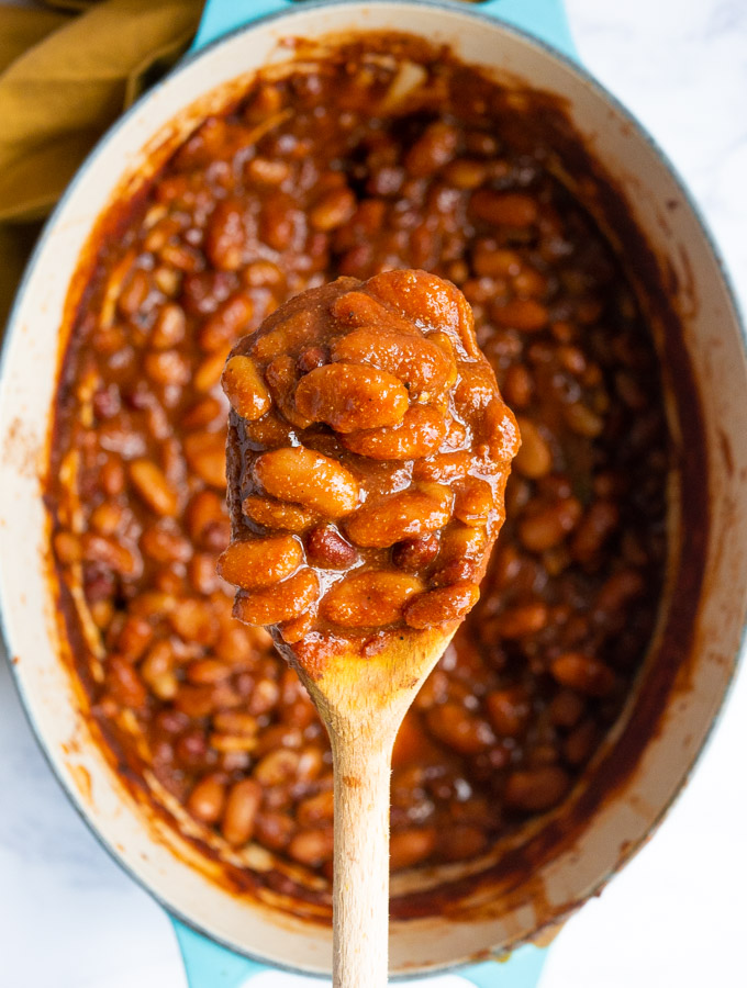 An over head shot of a wooden spoon filled with BBQ beans. Underneath the spoon is a blue le crueset pot, also fillde with beans.