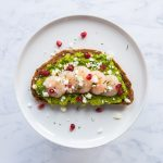 Minted pea purée tartine on a white plate, topped with prawns, crumbled feta cheese, pomegranate seeds and chopped mint on a marble background.