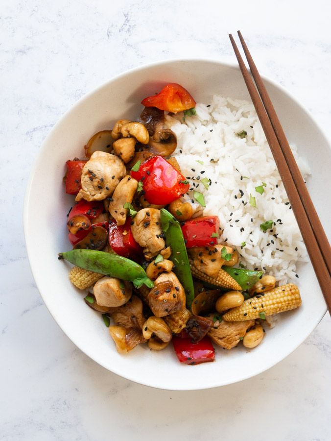 Cashew chicken in a white bowl with rice. A pair of chopsticks rest on the side of the bowl.