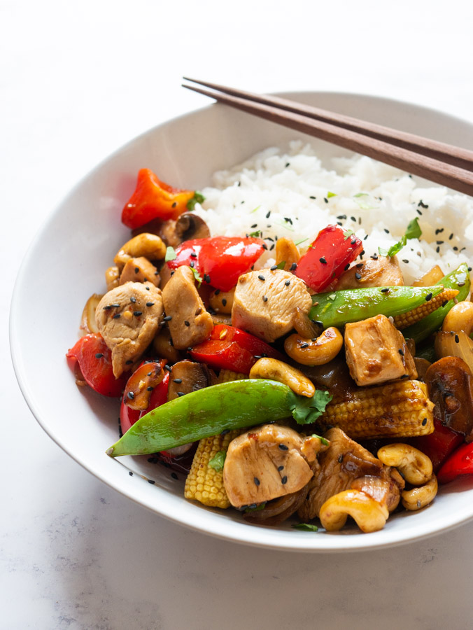 Cashew chicken in a white bowl with rice.