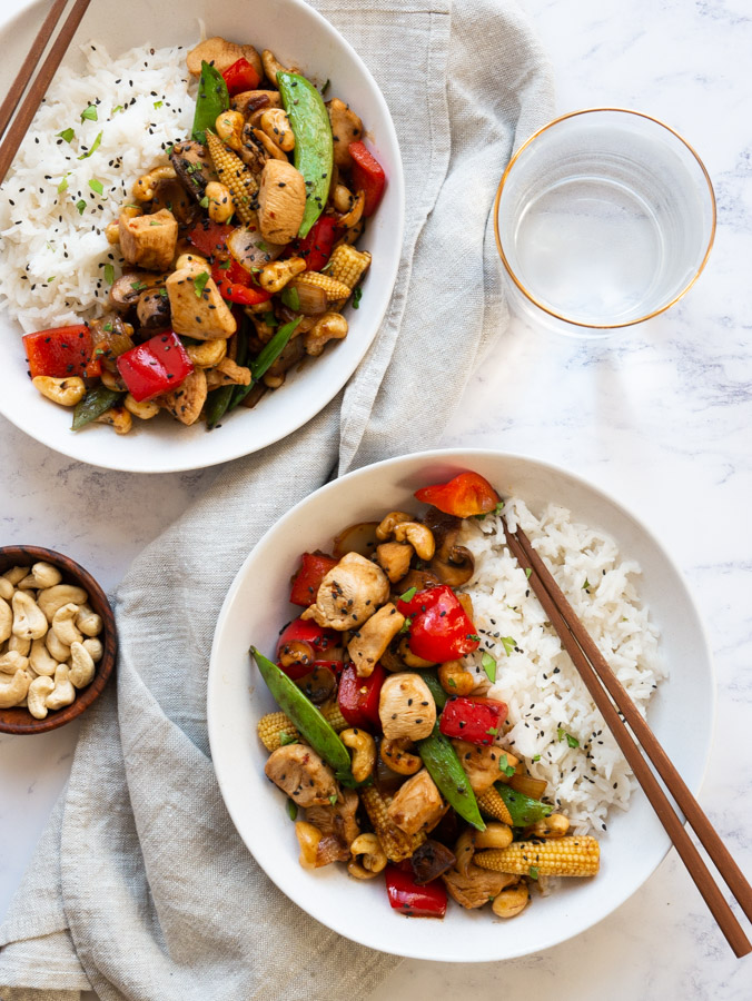 Two white bowls filled with Thai cashew chicken and served with rice. Pairs of chopsticks rest on the edges of the bowls. New to the bowls is a grey linen napkin, a glass of water and a wooden bowl filled with cashews.