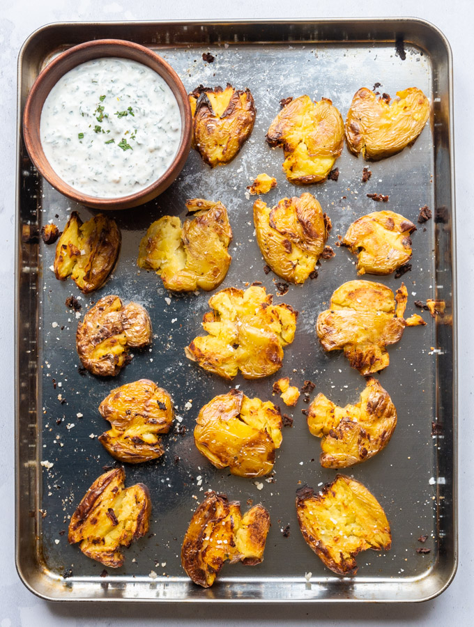 An overhead shot of a baking tray with crispy smashed potatoes. A wooden bowl filled with mint and feta dip sits in the tip left corner.