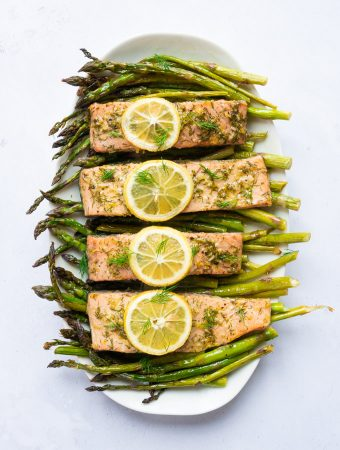 A white serving platter with roasted asparagus spears laying across it. On top of the asparagus is four marinated salmon fillets, each with slices of lemon on top.