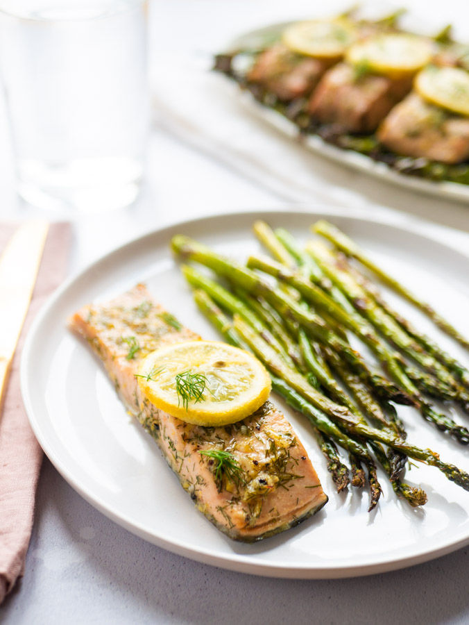 A salmon fillet on a white plate with baked asparagus spears.