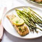 A salmon fillet that has been marinated in lemon, dill, honey and garlic and then baked on a white plate alongside baked asparagus.