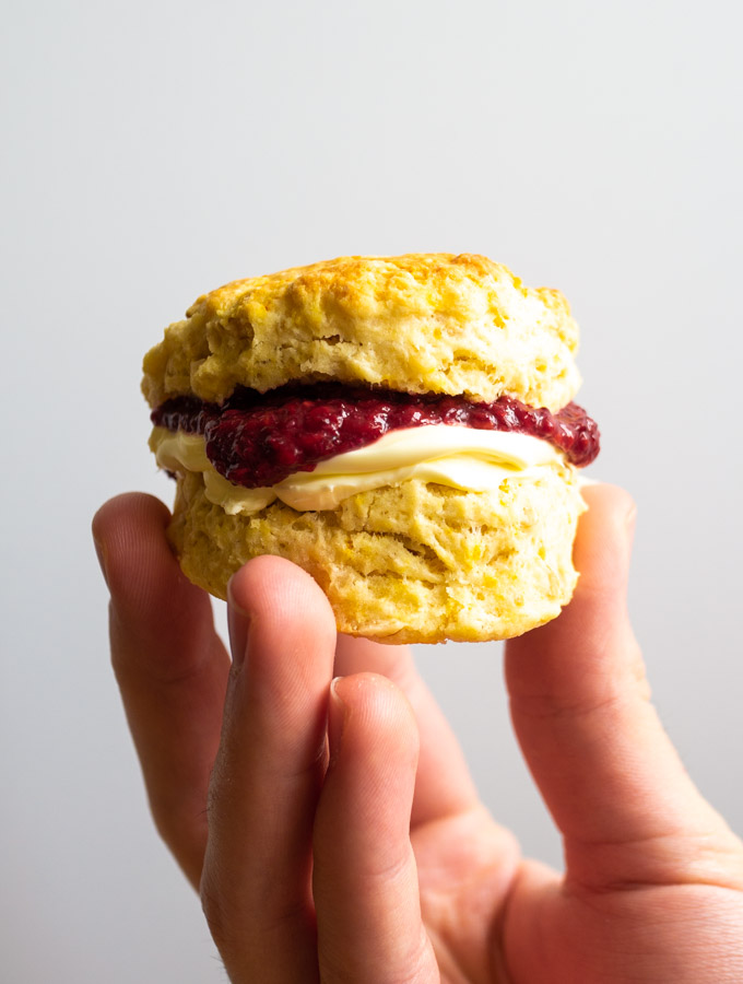A walnut and orange scone that has been cut in half and filled with clotted cream and raspberry jam. It is being held up in front of a white background.