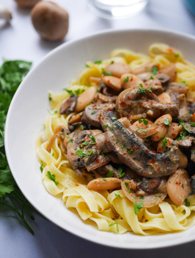 A close up photo of whitebean and mushroom stroganoff served with tagliatelle pasta in a white bowl.