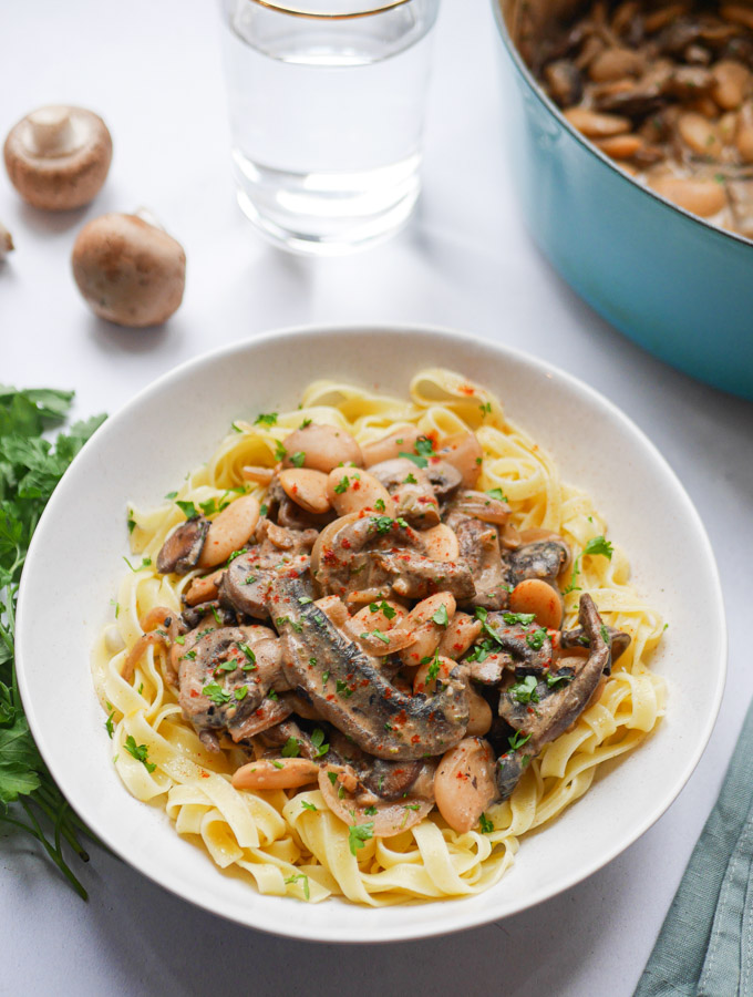 White bean and mushroom stroganoff served on tagliatelle in a white bowl.