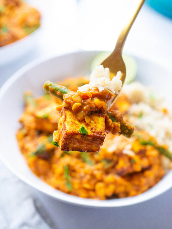 A close up image of a cube of paneer cheese with the lentil and green bean curry on a gold fork with rice.