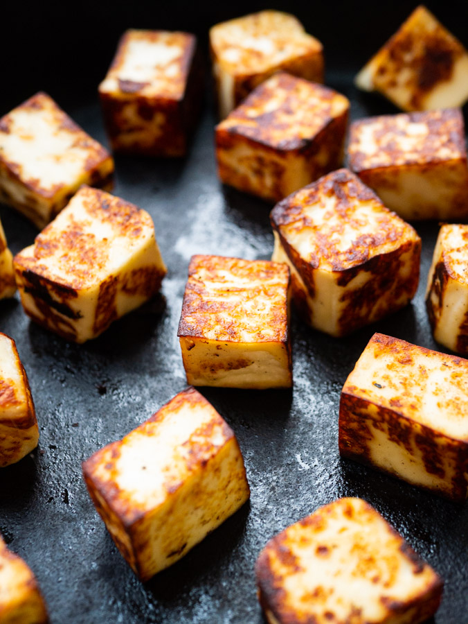 Cubes of paneer cheese in a cast-iron pan that have been cooked until they form a golden brown crust.