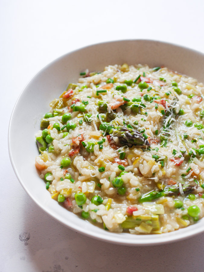 Pea & Asparagus Risotto with Bacon in a white bowl. The risotto is garnished with grated parmesan and chopped chives.