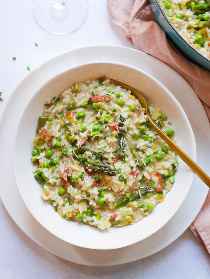 Pea & Asparagus Risotto with Bacon in a white bowl, sitting on top of a white plate. The risotto is garnished with grated parmesan and chopped chives.