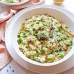 Asparagus risotto with peas and bacon in a white bowl with a gold fork in the bowl. Grated parmesan cheese and chopped chives have been used to garnish the risotto.