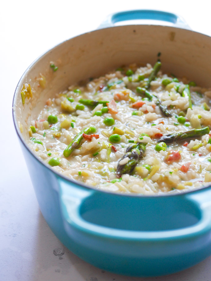 Pea & Asparagus Risotto with Bacon in a blue le creuset pot.