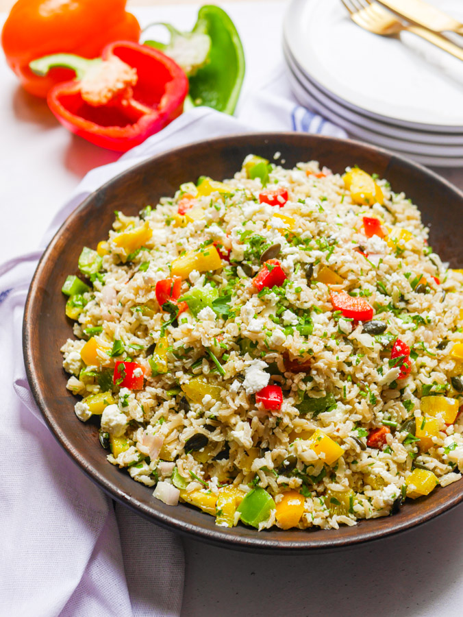 Bell Pepper Rice Salad in a wood bowl, garnished with crumbled feta cheese and chopped parsley. In the background are red, green and orange peppers and a stack of white plates.