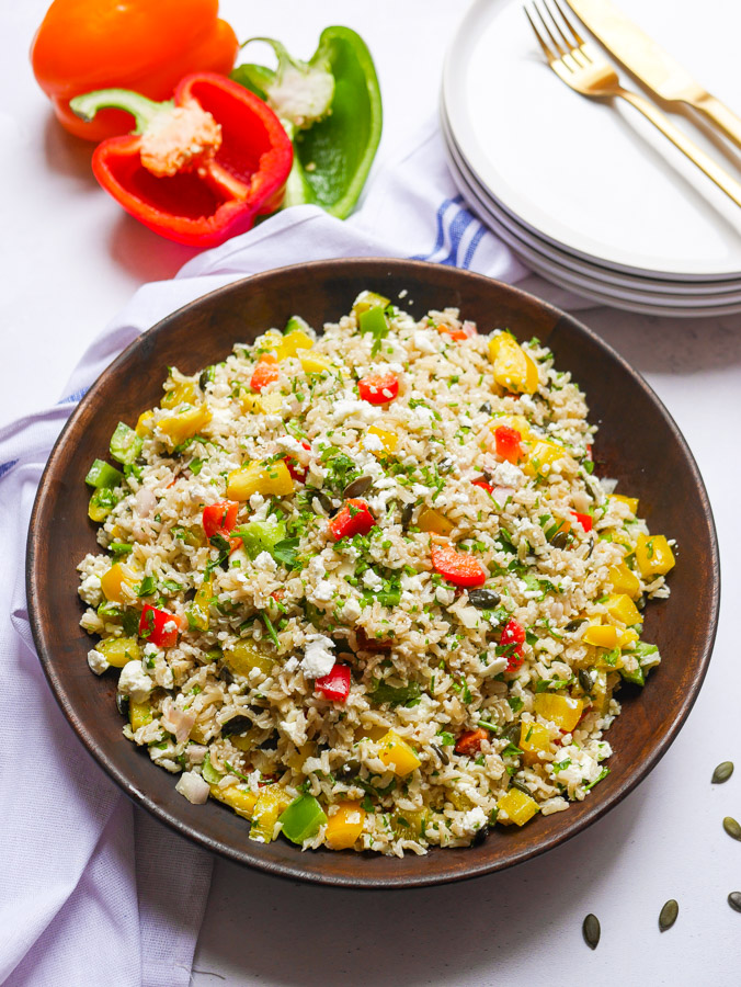 Bell Pepper Rice Salad in a wood bowl. A red, green and orange pepper is sat next to the bowl, as well as a stack of white plates with a golden knife and fork sat on top.