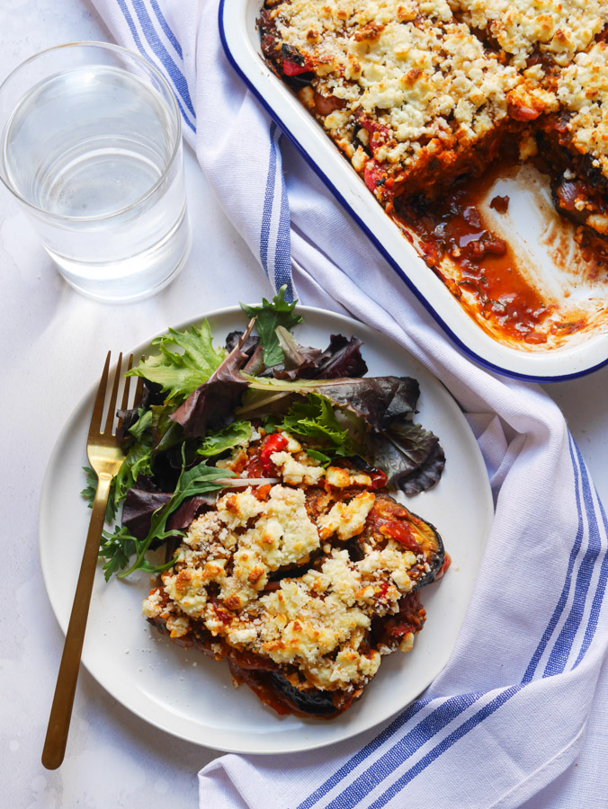 A birdseye shot of aubergine bake on a white plate with a side salad and a gold fork. The baking tray which the bake was cooked in is next to the plate with three more slices of aubergine bake. A blue and white napkin is placed in between the plate and baking tray.