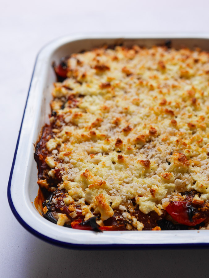 Roasted pepper and aubergine bake in a white baking tray. The feta and breadcrumbs on top are golden brown and crispy.