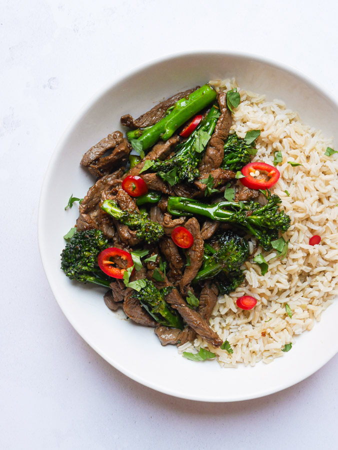 Vietnamese Beef & Broccoli Stir Fry in a white bowl, served with wholegrain rice.