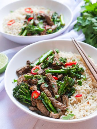 Two portions of Beef & Broccoli Stir Fry in white bowls. One bowl has chopsticks resting on the side. Both are served with wholegrain rice.