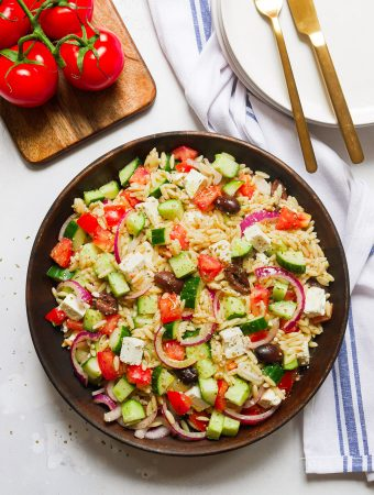 Greek Orzo Pasta Salad in a wooden bowl. Above the bowl are tomatoes on the vine and a stack of white plates with a knife and fork on top.