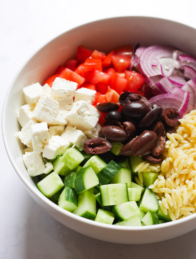 Chopped tomatoes, cucumber, red onion, feta cheese, olives and orzo pasta in a white bowl.