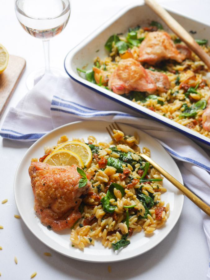 Mediterranean chicken and orzo bake on a white plate with a gold fork. Behind is a white roasting tray also containing the Mediterranean chicken and orzo bake. There is also a glass of white wine next to the plate.
