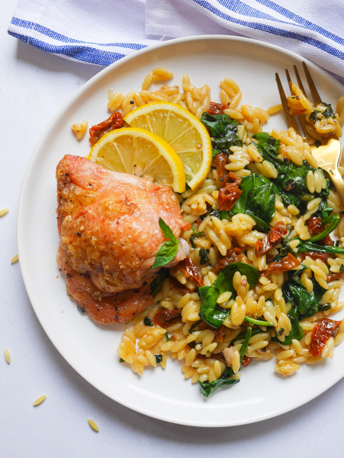 Mediterranean chicken and orzo bake on a white plate.
