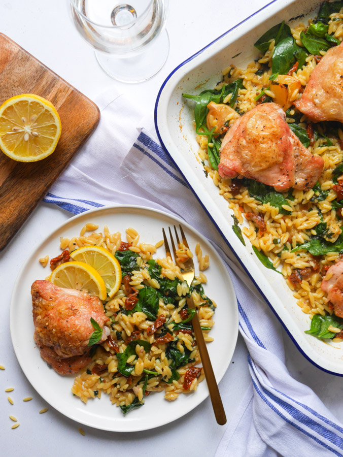 Mediterranean chicken and orzo bake on a white plate. Next to the plate is a roasting dish in which the chicken and orzo bake was cooked. There is also a wooden chopping boards with a chopped lemon on and a glass of white wine.