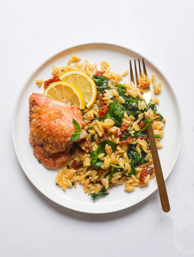 a roasted chicken thigh on a plate with orzo, sun-dried tomatoes and spinach. On the plate is a gold fork and slices of lemon for garnish.