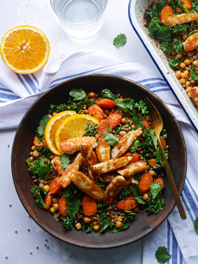 Halloumi couscous with carrots and chickpeas in a wooden bowl. Garnished with slices of orange and coriander leaves. The bowl is next to a roasting tray which is also filled with the carrot, chickpea and kale couscous.