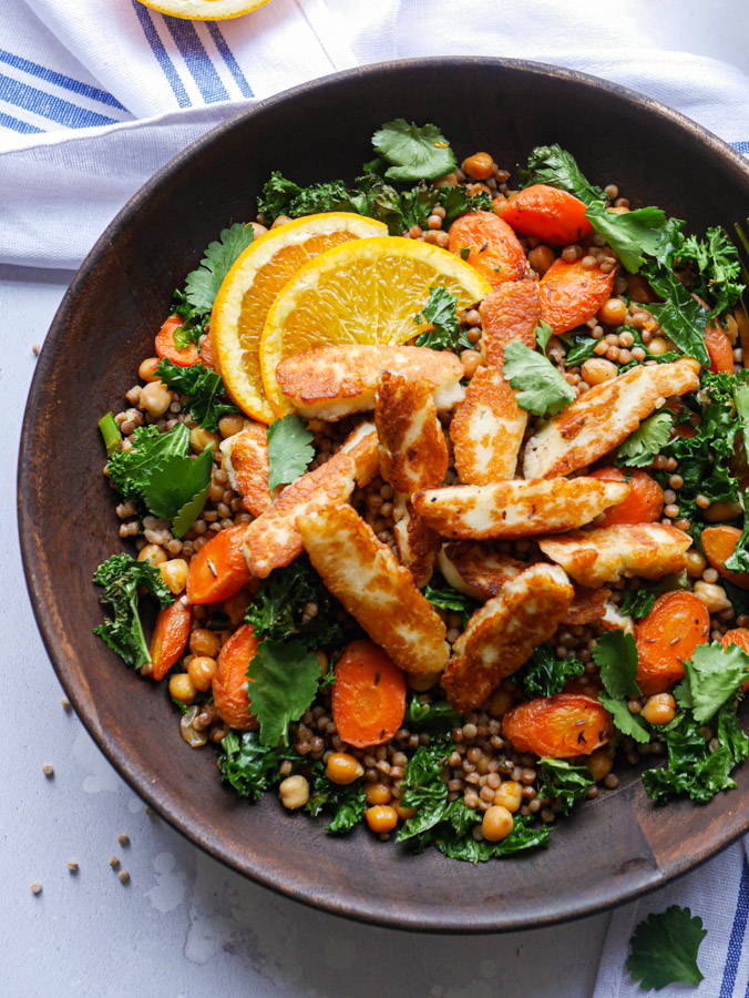 Halloumi and chickpea couscous with carrots and kale in a wooden bowl. Garnished with slices of orange and coriander leaves.