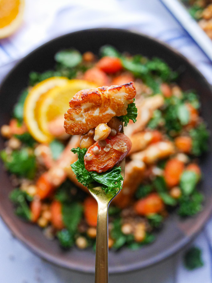 A fork filled with halloumi, roasted carrot, chickpeas, kale and couscous, being held above a bowl of halloumi couscous.