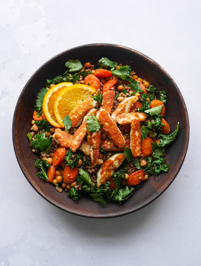 Halloumi couscous with carrots and chickpeas in a wooden bowl. Garnished with slices of orange and coriander leaves.