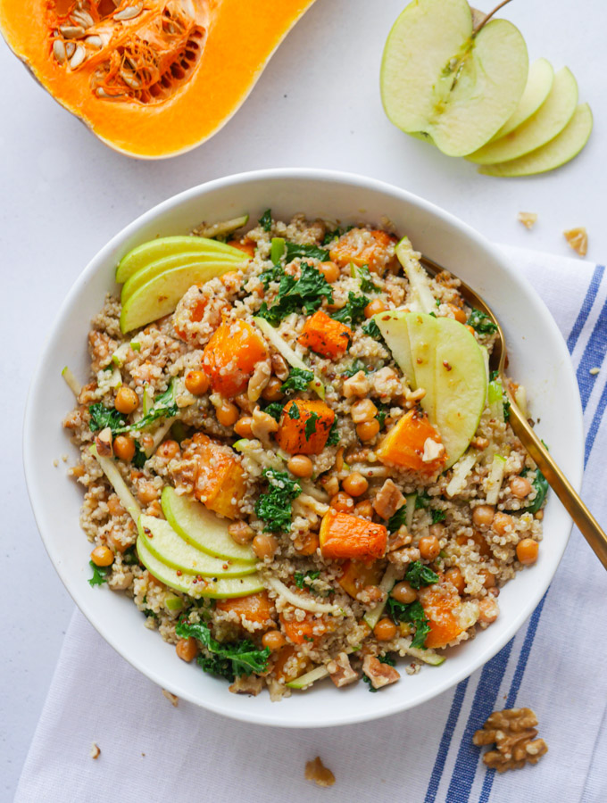 An overhead shot of roasted butternut squash salad with quinoa and apple in a white bowl. Next to the bowl is half a butternut squash and half an apple.